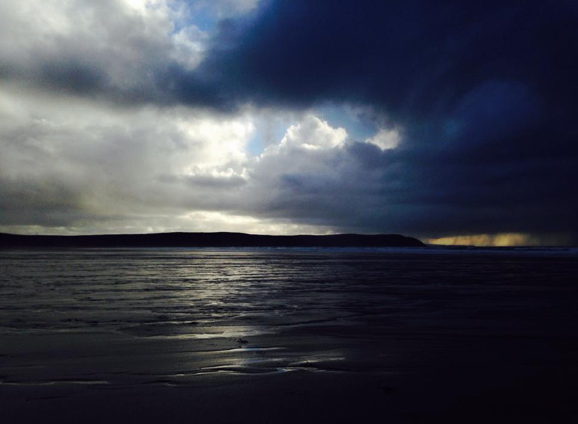 photo of light breaking in the distance over the sea off Woolacombe beach in Devon, England